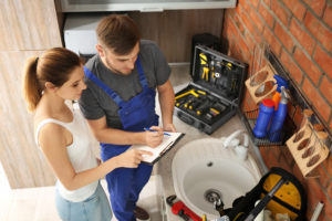 Professional licensed minneapolis plumber with client near kitchen sink